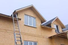 Escada que inclina-se contra uma casa nova da madeira da construção Imagem de Stock Royalty Free