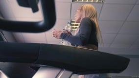 Escada rolante, cardio- treinamento, é contratada em sapatas em um simulador no gym, jovem mulher atlética saudável dos esportes video estoque