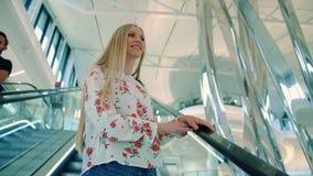Escada rolante da equitação da mulher na alameda De baixo do tiro da jovem senhora bonita que olha acima ao montar escadaria move video estoque