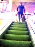 Escada rolante e homem obscuro no movimento Foto de Stock Royalty Free