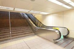 A escada rolante que move-se em uma estação de comboio do metro imagens de stock