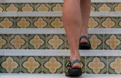Escadaria acima modelada da telha das caminhadas da mulher imagem de stock