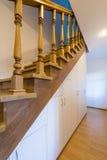 Escadaria com os trilhos de madeira cinzelados em uma construção entre assoalhos imagens de stock royalty free