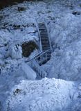 Escadaria de madeira congelada no gelo, coberto com os sincelos contra um campo de lava congelado coberto com o gelo e a neve foto de stock royalty free