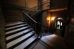 Escadaria do ferro forjado do vintage com etapas de madeira do corrimão e as de mármore imagem de stock