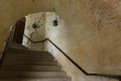 Escadaria espiral em uma construção de pedra dilapidada velha com um teto arcado Imagens de Stock Royalty Free