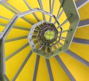Escadaria espiral longa com tapete do ywllow Imagens de Stock