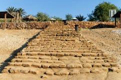Escadaria longa velha dos arenitos aproximadamente desbastados que conduzem à praia do Mar Morto em Jordânia foto de stock royalty free