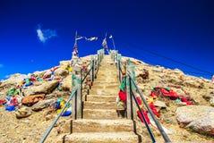 Escadas íngremes da rocha com as bandeiras coloridas que aumentam acima com o céu azul profundo fotografia de stock royalty free