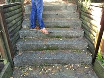 Escadas com pés nas calças de brim Imagem de Stock