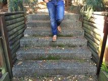 Escadas com pés nas calças de brim Fotografia de Stock Royalty Free