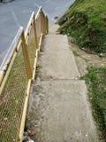 Escadas com trilhos e grama amarelos ao lado trânsito Fotos de Stock Royalty Free