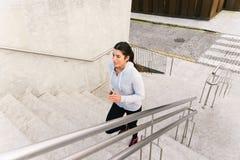 Escadas de corrida e de escalada da mulher desportiva fotos de stock royalty free