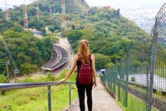 Escadas de descida levando da trouxa da menina nova do turista e apreciação da vista do pico de Jaragua, Brasil imagens de stock