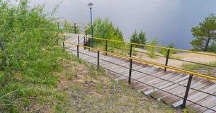 Escadas de madeira e de aço para baixo ao rio Fotografia de Stock