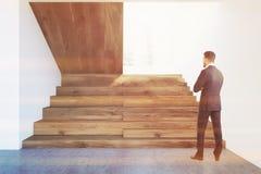 Escadas de madeira escuras no salão branco da parede, homem de negócios Foto de Stock Royalty Free