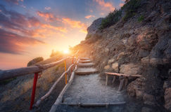 Escadas de pedra com os trilhos de madeira nas montanhas no por do sol Foto de Stock