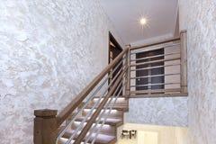 Escadas do carvalho com iluminação e do emplastro decorativo nas paredes imagem de stock