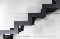 Escadas feitas do metal preto sobre a parede branca Foto de Stock Royalty Free