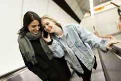 Escadas rolantes a do uso das jovens mulheres Fotos de Stock Royalty Free