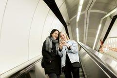 Escadas rolantes do uso das mulheres e utilização de um telefone celular Imagens de Stock Royalty Free