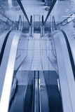 Escadas rolantes vazias no azul Foto de Stock Royalty Free