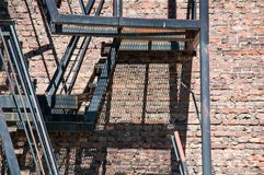 Escadas velhas do escape de fogo na fábrica Imagens de Stock