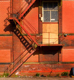 Escadas velhas oxidadas do escape de incêndio no armazém fotografia de stock