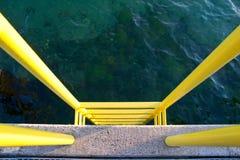 Escala amarilla en un embarcadero concreto Fotos de archivo