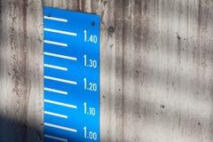 Escala azul de la medida del nivel de la marea en el muro de cemento imagen de archivo libre de regalías