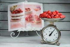 Escala da cozinha que pesa morangos Imagem de Stock