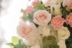 A escala das flores de matiz delicadas em um arco do casamento fotografia de stock royalty free