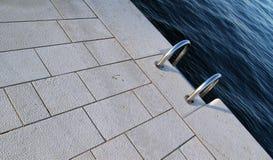 Escala de acero en el borde del agua imagen de archivo libre de regalías