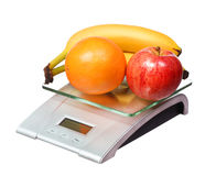 Escala de la comida con el plátano y la naranja de manzana de las frutas aislados Foto de archivo libre de regalías