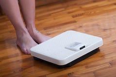 Escala de los pies de la mujer y del peso corporal Fotos de archivo libres de regalías