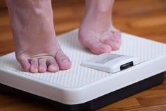 Escala de los pies de la mujer y del peso corporal Foto de archivo libre de regalías