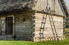 Escala de madera que se inclina en una choza en el país Foto de archivo