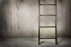 Escala de madera vieja en una pared del cemento Fotos de archivo