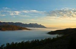Escala de montanha e um vale da névoa na aurora Fotos de Stock Royalty Free