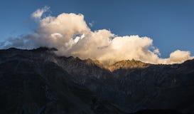 Escala de montanhas por Kazbegi, Geórgia no por do sol imagens de stock