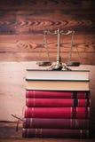 Escala de oro encima de la pila de libros de ley Imagen de archivo libre de regalías