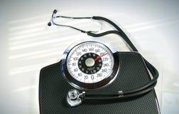 Escala del peso con el estetoscopio Fotografía de archivo libre de regalías