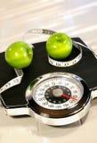 Escala del peso con las manzanas verdes Fotografía de archivo libre de regalías