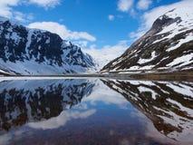 Escala nevado da reflexão no lago da montanha alta noruega Imagens de Stock Royalty Free