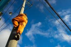 Escalada asiática do eletricista alta no polo para reparar o sistema bonde Foto de Stock