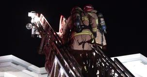 Escalada da escada dos sapadores-bombeiros no telhado filme