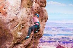 Escalada de la muchacha en la cumbre de la montaña Foto de archivo