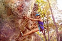 Escalada de la mujer con el arnés en área del bosque Fotos de archivo