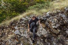Escalada del hombre joven en una pared de la piedra caliza Imagen de archivo