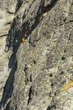 escalada do Multi-passo - um partido de dois montanhistas no passo na parede do maciço Fotografia de Stock